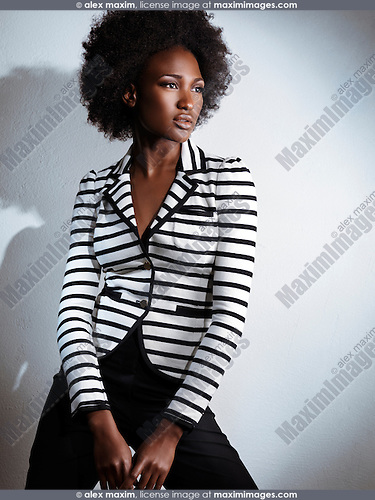 Beautiful african american woman wearing black pants and a stripy white and black top. Artistic fashion photo.