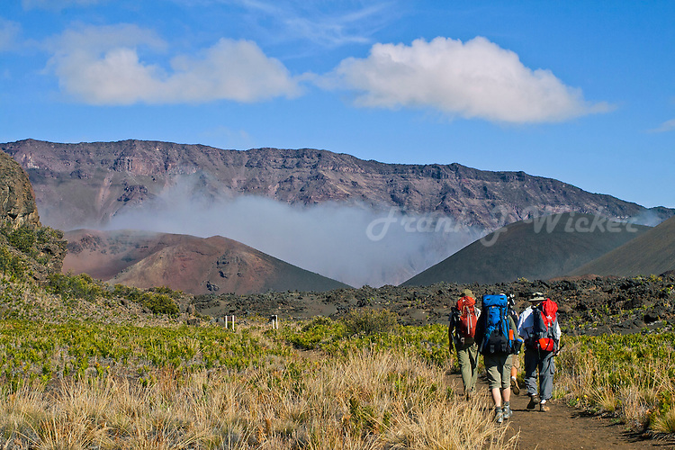 Three male hikers with red and blue backpacks inside the crater of HALEAKALA NATIONAL PARK on Maui in Hawaii