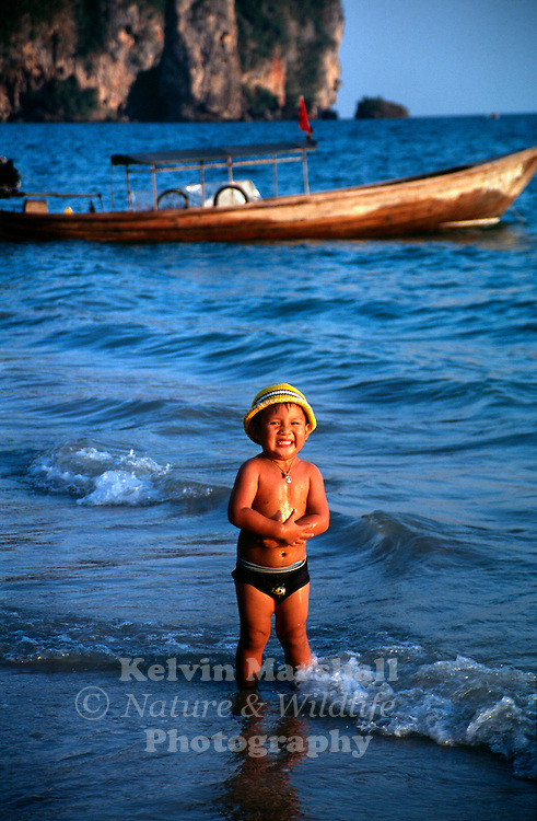 Young Thai child with a big smile comes down to the beach for a swim in the late afternoon. AoNang - Krabi Province - Thailand.