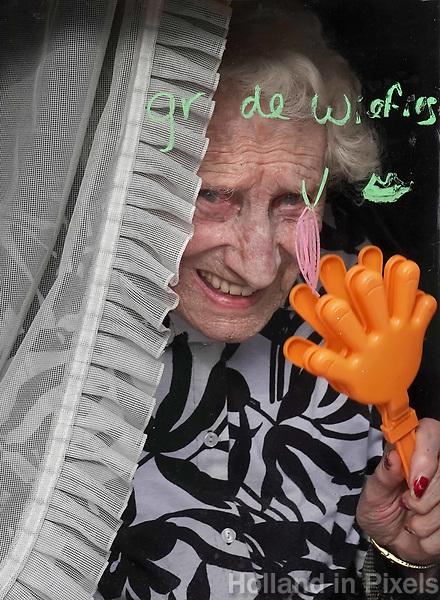 Nederland  Oss  -  2018. Halfvastenoptocht in Oss. Jaarlijkse afsluiting van het Carnaval seizoen.  Oudere vrouw zwaait naar de optocht.   Foto Berlinda van Dam / Hollandse Hoogte