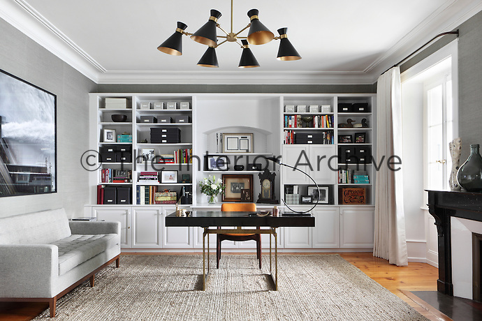 1950s style furniture and fittings add a distinctly retro chic to this spacious study, furnished with built-in, wall-to-wall shelving and wood floors