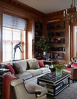 The study has a warm and cosy feel with wood panelling and built-in book shelves. The sofa, covered in a Kravet fabric, the nailhead-trimmed armchair, in a Holland & Sherry fabric, and cocktail table are all custom made. The club chair is by Robert Allen, the sculpture is by Eric Fischl and the carpet is by Beauvais.