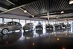 Een rij tweedehands auto's weerspiegelt in de vloer van een autodealer.