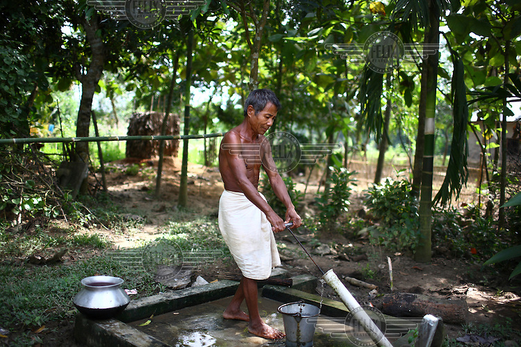A Garo man uses a hand suction pump to draw water. The Garo (or Mandi, as they refer to themselves) are an ethnic minority thought to be of Tibeto-Burmese origin. Prior to British rule they were mostly anamists but missionary work led the majority to convert to Christianity. The Garo of the Madhupur forest have long been under the threat of eviction by the government and the forest that they gain much of their livelihood from is being rapidly destroyed by unregulated logging.