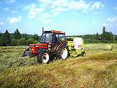 Farm tractor pulling round baler in field making round bales of hay on a hot summere day. to be used to feed cattle