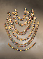 Mycenaean gold necklaces from the Mycenae chamber tombs, Greece. National Archaeological Museum Athens.<br /> <br /> From top to bottom: <br /> <br /> Top four  necklaces in the shape of papyrus flowers .<br /> <br /> Fifth necklace down in the shape of Ivy leaves from tomb 91 Cat No 3186<br /> <br /> <br /> Bottom necklace with beads in the shape of hangimng scrolls from tomb 25 Cat No 2478.