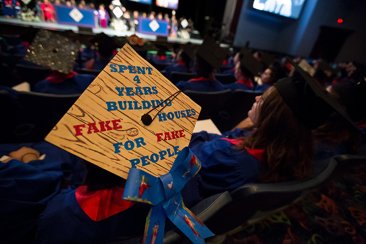 A student with a elaborately decorated motor board listens to remarks Saturday, June 10, 2017, during the DePaul University School of Music and The Theatre School commencement ceremony at the Rosemont Theatre in Rosemont, IL. (DePaul University/Jeff Carrion)