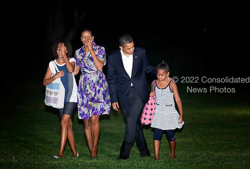 Washington, DC - July 12, 2009 -- United States President Barack Obama (2R), First Lady Michelle Obama (2L) and the daughters Malia (L) and Sasha (R) walk from Marine One on the South Lawn of the White House, Sunday, July 12, 2009.  President Obama and the first family returned home to the White House in the early morning after a trip overseas to Russia, Europe, Africa and a G-8 meeting..Credit: Brendan Smialowski - Pool via CNP