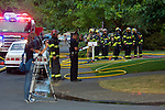 All accounted for, the fire crew recounts the call as a TV vidoegrapher records the aftermath.