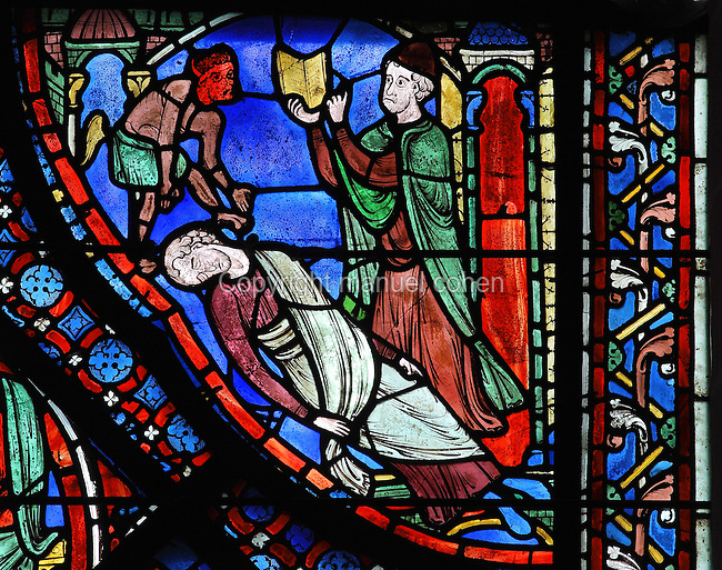 Hermogenes, furious at Philetus' conversion by St James, casts a magic spell on him to send him to sleep, with the help of the red-faced devil. Section of Hermogenes casting a spell on Philetus, 1210-25, from the Life of St James window in the ambulatory of Chartres Cathedral, Eure-et-Loir, France. This window tells the story of the life of St James the Greater, apostle of Jesus and son of Zebedee. It is situated next to the apostles chapel. Chartres is a stop on the pilgrimage route to Compostela, where James' relics lie. Chartres cathedral was built 1194-1250 and is a fine example of Gothic architecture. Most of its windows date from 1205-40 although a few earlier 12th century examples are also intact. It was declared a UNESCO World Heritage Site in 1979. Picture by Manuel Cohen