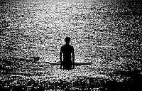 Rick Wilson Photo--7/14/04--A lone surfer waits for non-existent waves in the unusually calm surf of the Atlantic Ocean at Vilano Beach, Florida.