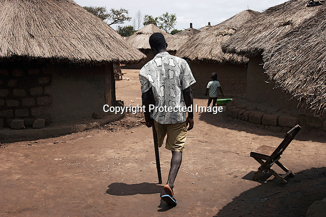 PAICHO, UGANDA AUGUST 3: Onkom Geoffrey, age 25, walks with crutches to his home on August 3, 2005 in Paicho, a camp for displaced people in Northern Uganda. He was injured by the Lord's Resistance Army (LRA) and was later taken to a hospital in Gulu, the provincial capital. The rebel group has brought terror to Northern Uganda for almost twenty years, fighting the Ugandan government. The victims are usually children, which are abducted and used as child soldiers and sex slaves. Many of the abducted children are forced to perform gruesome acts and are usually brainwashed when initiated in the LRA. About 60.000 people live in the camp in bad conditions. (Photo: Per-Anders Pettersson)....