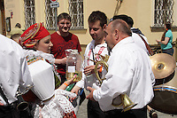Young woman at the ride of Kings in Prague, dressed in typical Moravian costume is serving new wine to the musicians at the event.<br /> <br /> Twelve-year-old Frantisek Libosvar dressed as a girl and with a rose in his mouth leads the royal procession during Ride of the Kings as part of Navalis Celebrations on May 15, 2015 in Prague, Czech Republic. The Navalis Saint John's celebrations take place to commemorate Czech saint and Prague native, Saint John of Nepomuk, patron of all people of the water. <br /> <br /> <br /> The Ride of the Kings takes place during the spring, as a part of the Pentecost traditions . A group of young men ride through a Prague in a ceremonial procession. The ride is headed by chanters, followed by pageboys with unsheathed sabres who guard the King &ndash; a young boy with his face partially covered, holding a rose in his mouth &ndash; and the rest of the royal cavalcade. The King and pageboys are dressed in women&rsquo;s ceremonial costumes, while the other riders are dressed as men. The entourage rides on decorated horses, stopping to chant short rhymes that comment humorously on the character and conduct of spectators. The chanters receive donations for their performance, placed either in a money box or directly into the riders&rsquo; boots. The King&rsquo;s retinue returns home after a few hours of riding, and celebrates in the evening at the house of the King with a small feast, music and dancing. The practices and responsibilities of the Ride of the Kings are transmitted from generation to generation. The traditional paper decorations for the horses and the ceremonial costumes, in particular, are made by women and girls familiar with the processes, colour patterns and shapes specific to each village.