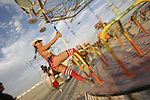 A woman holds onto a spinning merry-go-round using just her right leg on the playa of Black rock Desert, Nevada