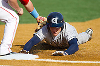 Rand Ravnaas #33 of the Georgetown Hoyas dives back into first base against the Delaware State Hornets at Gene Hooks Field on February 26, 2011 in Winston-Salem, North Carolina.  Photo by Brian Westerholt / Four Seam Images