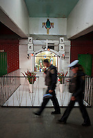 Two police pass an altar of the Virgin of Guadalupe in the Central de Abastos one of the world's largest food market. Aromas y Sabores with Chef Patricia Quintana