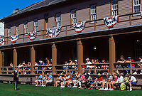 TOURISTS CLAP ALONG AS A MUSICIAN PERFORMS ON THE PARADE GROUNDS OF FORT MACKINAC ON MACKINAC ISLAND, MICHIGAN.