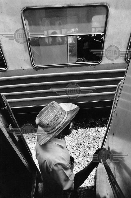 A man on a train travelling through central Cuba.
