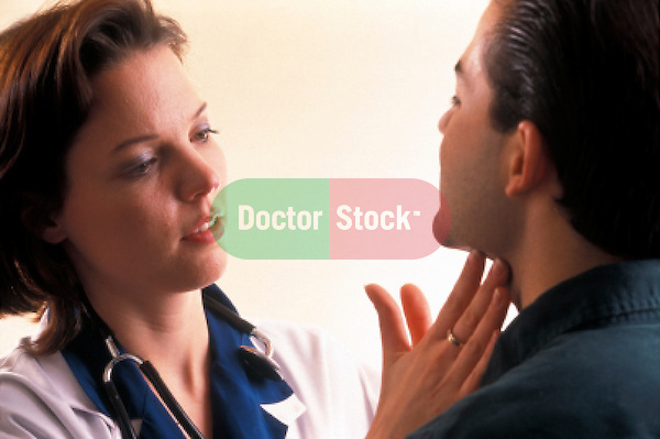 young female doctor examing male patient's throat neck glands