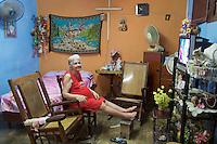 Havana, Cuba. La Habana Vieja (Old Habana). An elderly lady at home with her TV.