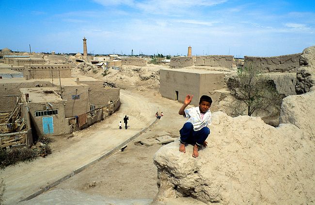 UZBEKISTAN, KHIVA, OLD TOWN, BOYS SITTING ON TOWN WALL