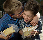 brothers, young boys having fun eating cinnamon rolls, Glen Haven, Colorado, summer, model released (MR - #98).
