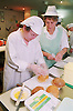 Woman with Downs Syndrome and supervisor making cobs in kitchen,