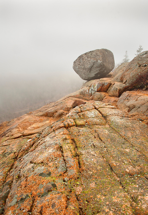 In fog, Bubble Rock rest precariously on the cliffs at Acadia National Park, Maine, USA