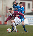 Arbroath's Ross Chisolm holds off Queen of the South's Paul Burns.