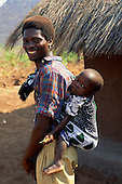 Yumba, Tanzania. Smiling father with a baby slung behind him; Lake Tanganyika.