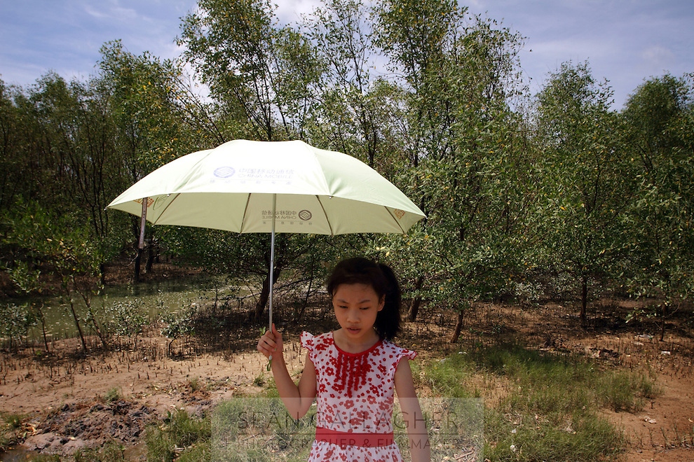 A young girl walks near the mangroves found in Zhanjiang, Guangdong Province. Over the past century, the world has lost over 50% of its coastal mangroves. They have been cleared mainly to make way for commercial shrimp and fish farms. The unique trees which live in salt water are valued for the ability to protect shorelines and are home to a diverse array of flora and fauna. 2010