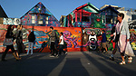 People walk past the vibrantly painted Bear Trap Studios on the Venice Beach Ocean Front Walk .