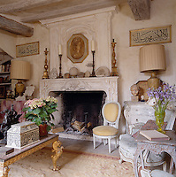 The living room has a vast stone fireplace and is furnished with with a mixture of antiques and objects collected on David Hare's travels
