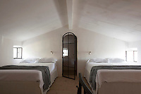 An attic bedroom is furnished with a pair of double beds with a door to the ensuite bathroom beyond