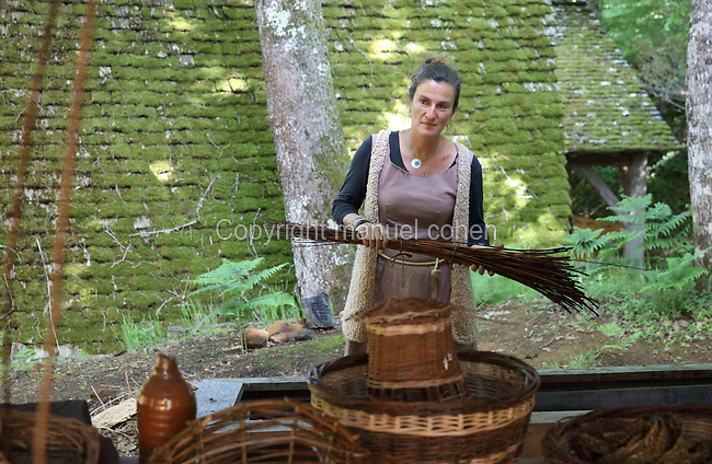 Aurelie Paillard, basketmaker, at work in the basketmakers' workshop at the Chateau de Guedelon, a castle built since 1997 using only medieval materials and processes, photographed in 2017, in Treigny, Yonne, Burgundy, France. The Guedelon project was begun in 1997 by Michel Guyot, owner of the nearby Chateau de Saint-Fargeau, with architect Jacques Moulin. It is an educational and scientific project with the aim of understanding medieval building techniques and the chateau should be completed in the 2020s. Picture by Manuel Cohen