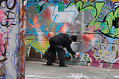 Young man paints graffiti on a wall at the South Bank, London.