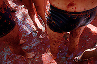 People stand barefoot in tomato pulp during La Tomatina festival in Bunol, Spain, 31 August 2006. La Tomatina is a tomato fight held annually in the town of Bunol, close to Valencia. Approximately 40,000 people from all over the world arrive to fight in the battle in which about 50 tons of over-ripe tomatoes are thrown in the street. During the one hour battle everybody fights everybody by throwing squashed tomatoes. The origin of this event is unknown but the Tomatina fights have been recorded since 1945.