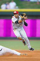 Erik Gonzalez (10) of the Carolina Mudcats follows through on his throw to first base to complete a double play against the Winston-Salem Dash at BB&T Ballpark on June 6, 2014 in Winston-Salem, North Carolina.  The Mudcats defeated the Dash 3-1.  (Brian Westerholt/Four Seam Images)