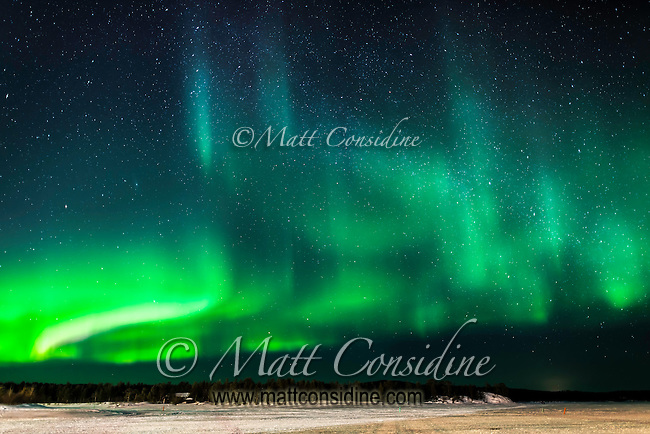 Strong green curtain aurora over ice lake, (Photo by Travel Photographer Matt Considine)