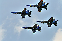 Four US Navy Blue Angels jets flying in tight formation