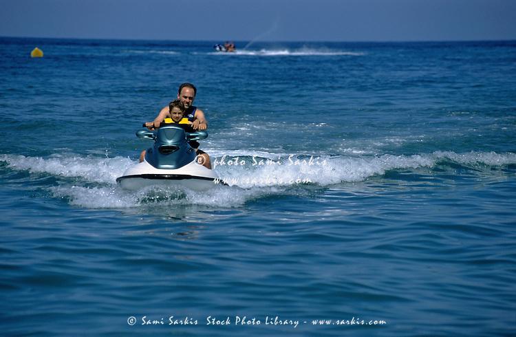 Father and son riding a jet ski, Bastia, Corsica, France.