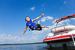 USA, Missouri, Stockton, Stockton Lake, boy (6-7) jumping off boat