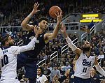 Akron forward Jaden Sayles, center,  grabs a rebound against Nevada in the second half of an NCAA college basketball game in Reno, Nev., Saturday, Dec. 22, 2018. (AP Photo/Tom R. Smedes)