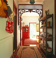 One wall of the hallway is adorned with a row of floppy hats and the shiny wooden floors are covered with colourful rugs