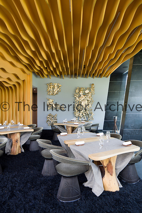 The restaurant has a moulded ceiling and features natural wood tables teamed with armchairs by Warren Platner