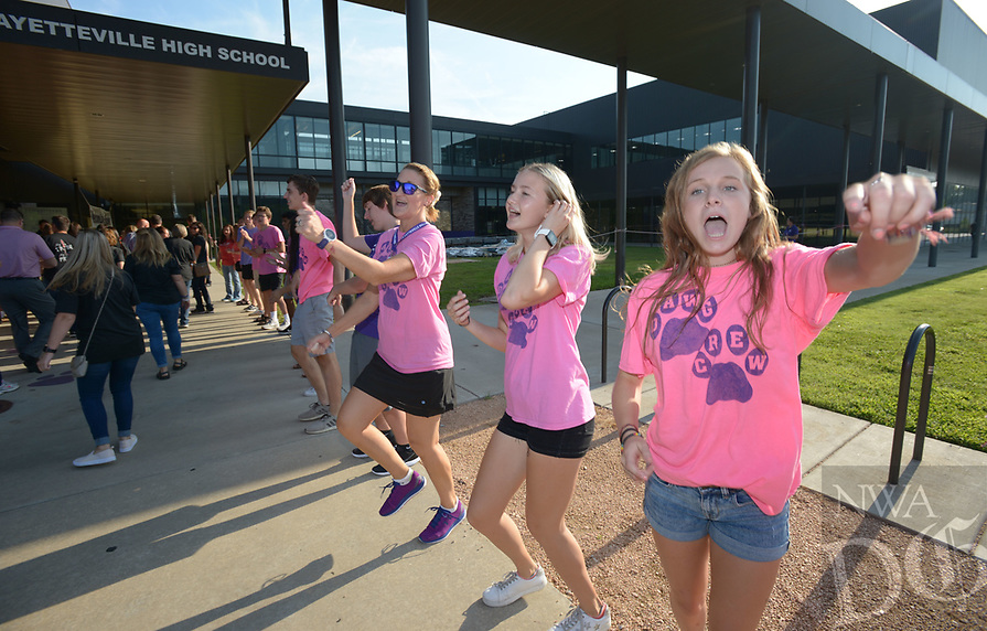 NWA Democrat-Gazette/ANDY SHUPE<br /> Grace Litzinger (right) and Gracie LeFevre, both juniors at Fayetteville High School and members of the school's Dawg Crew student ambassadors, dance Friday, Aug. 10, 2018, while greeting teachers and staff of the disctrict during Fayetteville Public Schools annual Convocation ceremony in Bulldog Arena on the Fayetteville High School campus. The event, which features performances by a combined choir and the high school band as well as awards and presentations, serves as a kickoff to the school year which begins Monday.