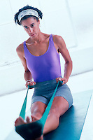Woman using a physical therapy band during workout.