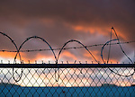 Sunset in Long Island. Barbed wire tops chain link fence separating properties.