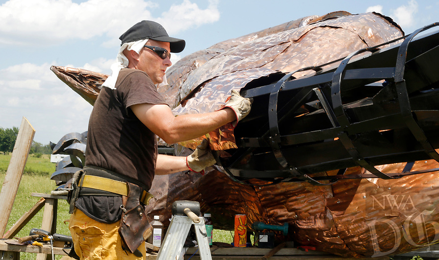 NWA Democrat-Gazette/DAVID GOTTSCHALK Metal worker-artist Lee Koehn places a sheet of copper on the rear leg area of a 25 foot tall boar Wednesday, June 6, 2018, at the studio of artist Eugene Sargent in rural Washington County. Sargent was commissioned by Slinkard to design and build the boar that will be installed Sunday, June 10, 2018 and a five foot tall base at the company office at 4148 West Matin Luther King Jr. Boulevard in Fayetteville.