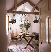 A view through an open door to a home office decorated in neutral tones. The room has exposed rafter beams and a zebra pattern flooring. Lamps and flower arrangements stand on a wooden trestle table and drying flowers hang from the beams.